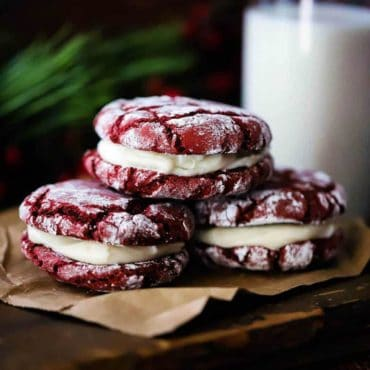 Three red velvet sandwich cookies stacked on a piece of brown paper next to a glass of milk.