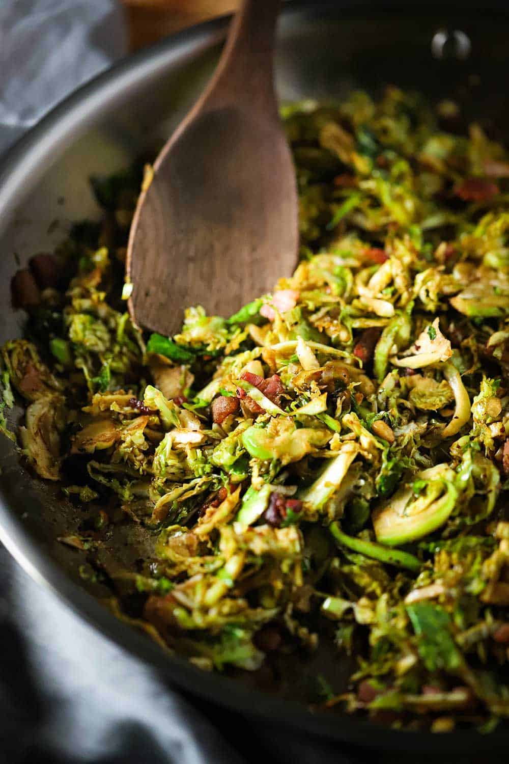 A large steel skillet filled with cooked shaved Brussels sprouts with pancetta and balsamic and a wooden spoon in the middle of the pan.