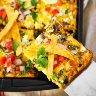 A slice of a Mexican frittata being lifted out of a sheet pan of the dish.