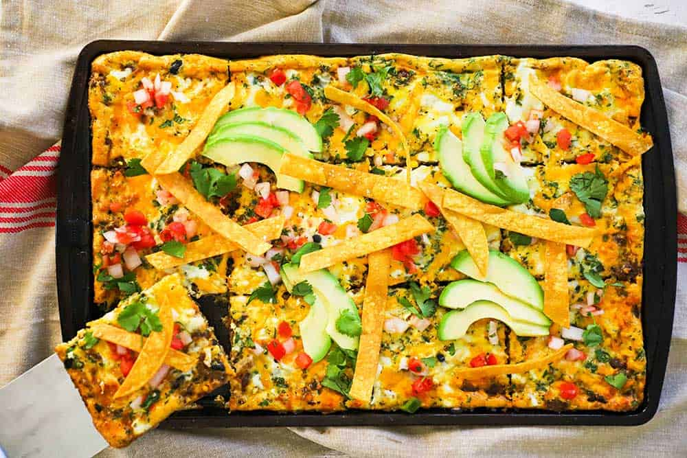 A fully cooked sheet-pan Mexican frittata with a person removing a slice with a spatula.