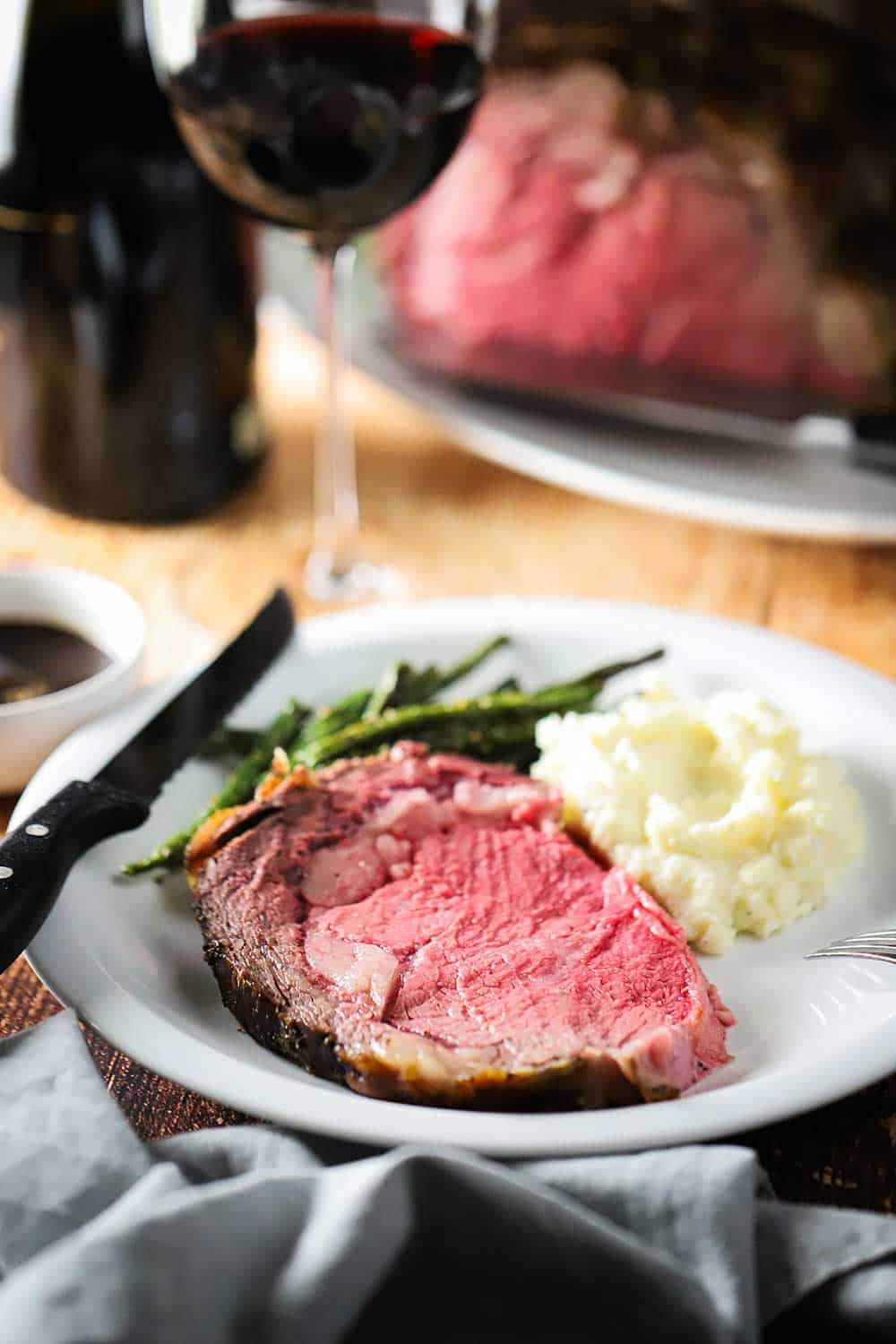A white dinner plate filled with a slice of roast beef next to helping of mashed potatoes and green beans.