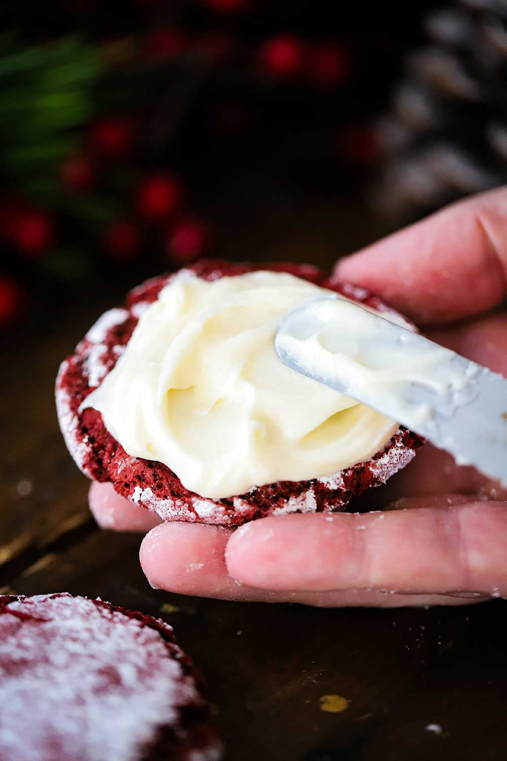 An off-set spatula spreading cream cheese frosting on the flat side of a red velvet cookie.