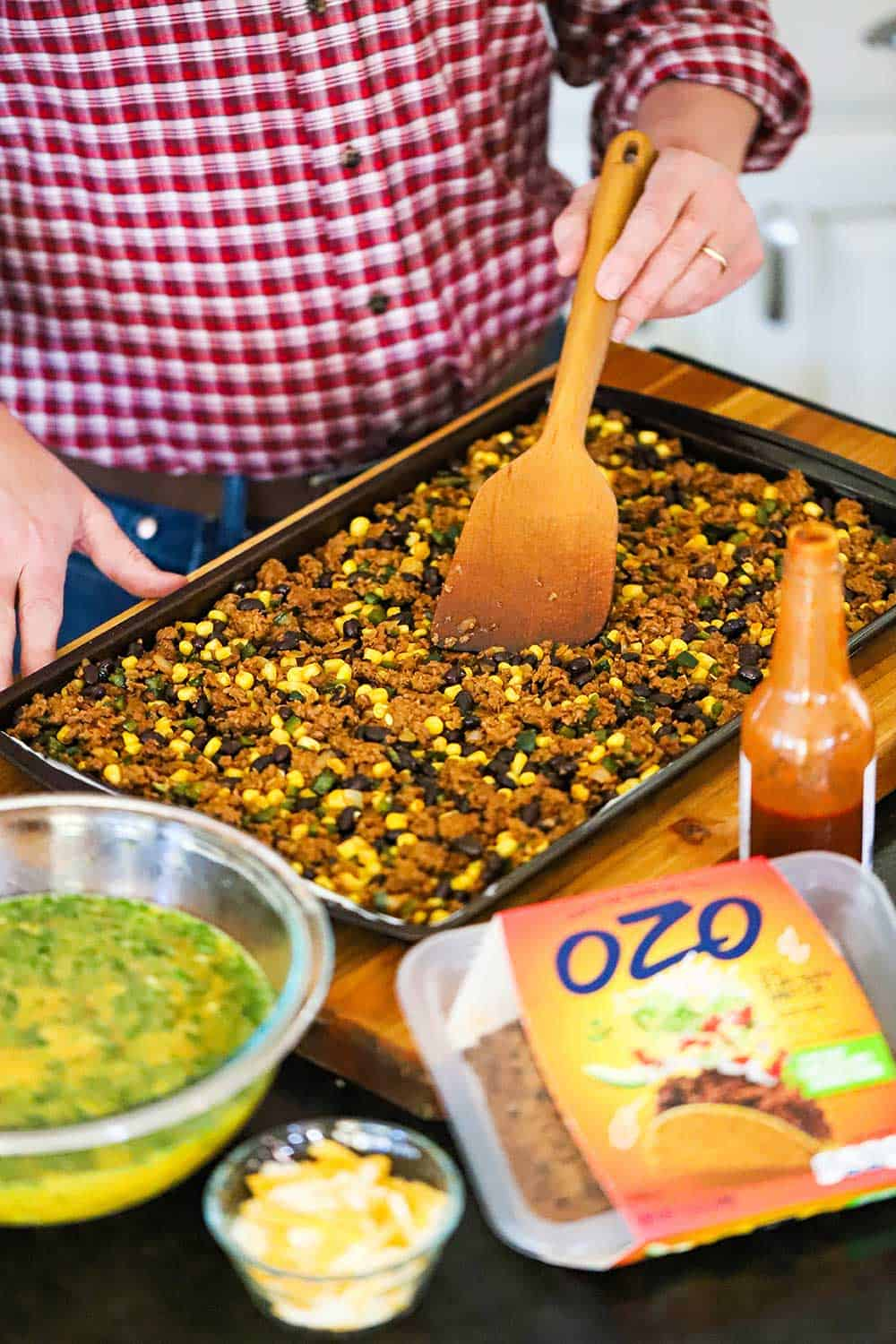 A person using a wooden spatula to spread a plant-based Mexican mixture over the base of a rimmed baking sheet pan.