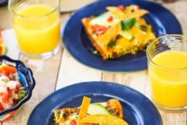 Mexican frittata squares on a couple of blue plates next to glasses of orange juice.