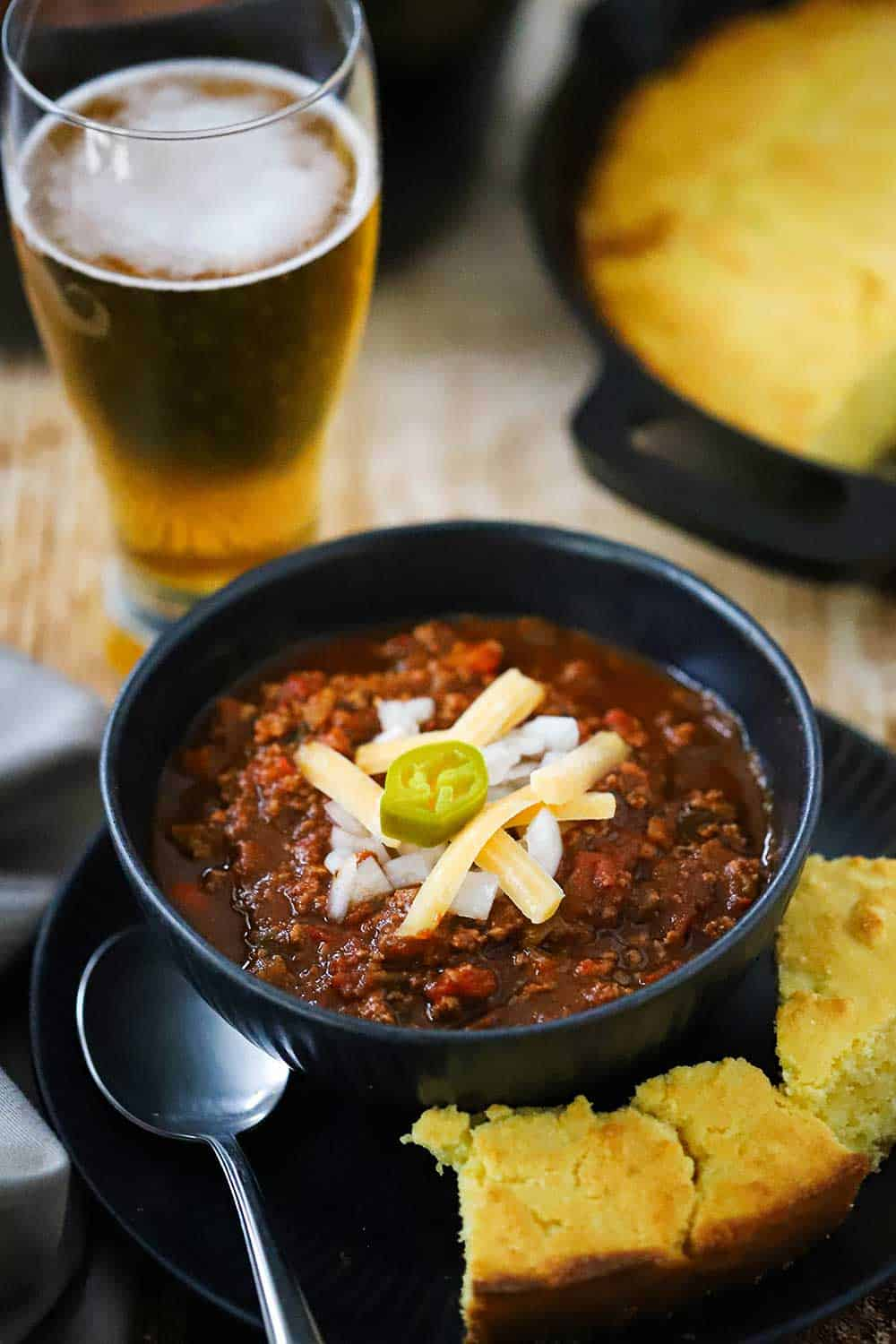 A dark bowl filled with turkey chili topped with shredded cheese and a sliced jalapeno all sitting next to a tall glass of beer.