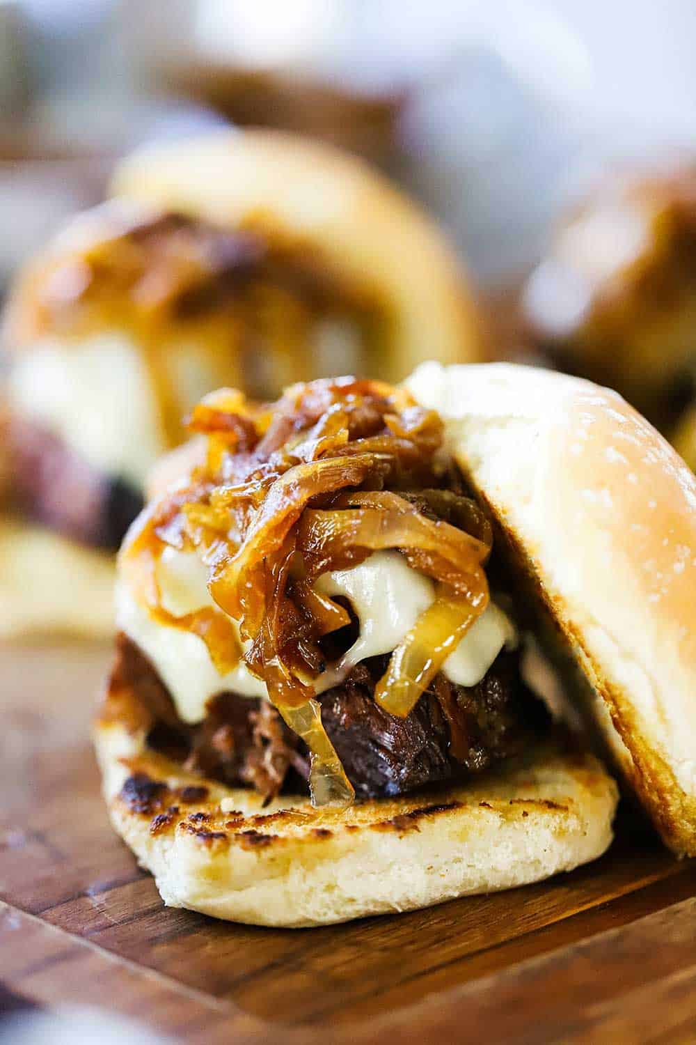 A leftover pot roast slider sitting on a cutting board that is topped with a mound of caramelized onions and melted Swiss cheese.