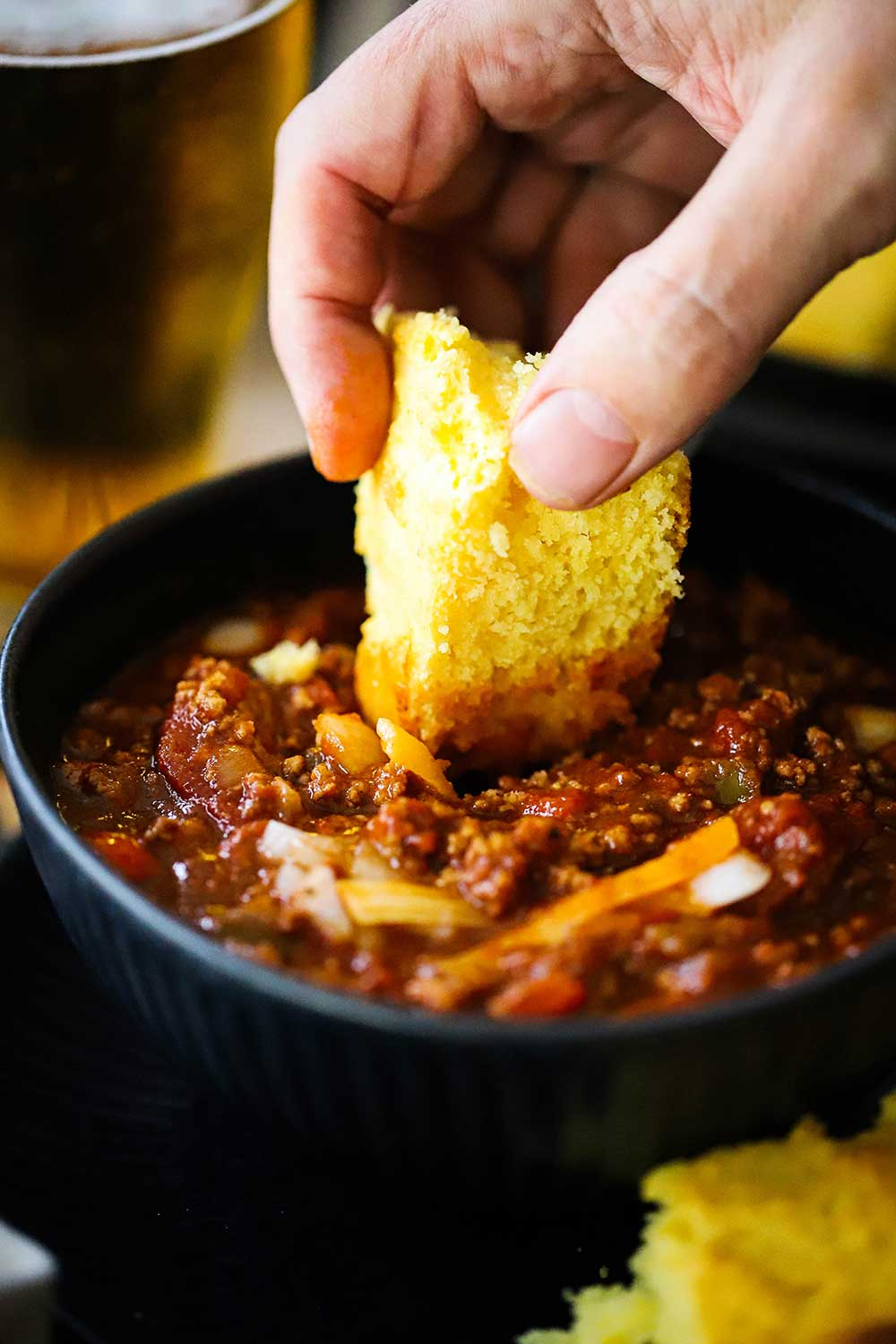 A hand dipping a slice of homemade cornbread into a bowl of turkey chili.