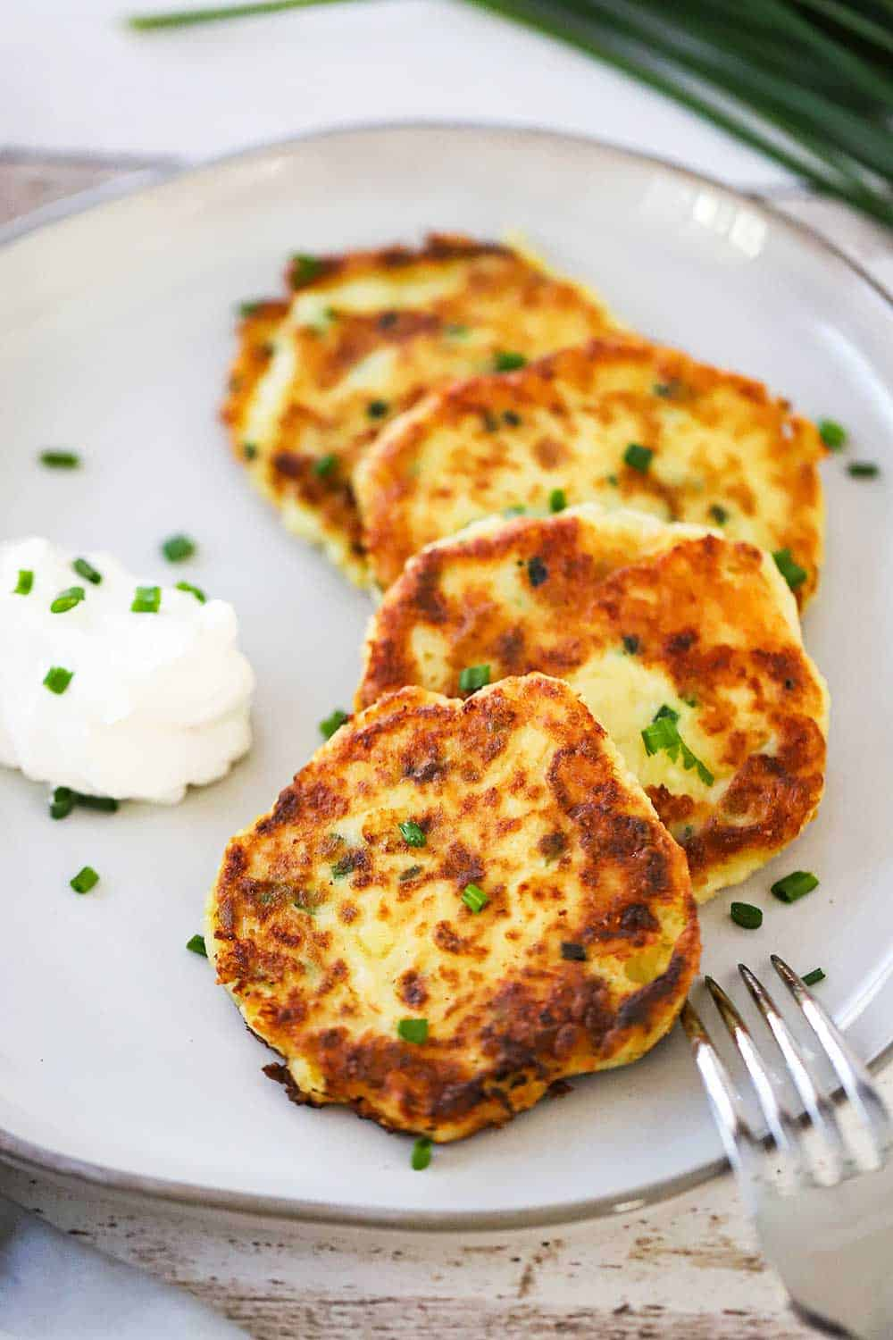 5 leftover mashed potato cakes layered on a plate with a dollop of sour cream nearby and sprinkled with chopped chives.