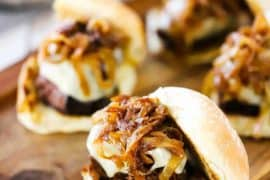 Four pot roast sliders each topped with melted Swiss cheese and caramelized onions all on a small cutting board.