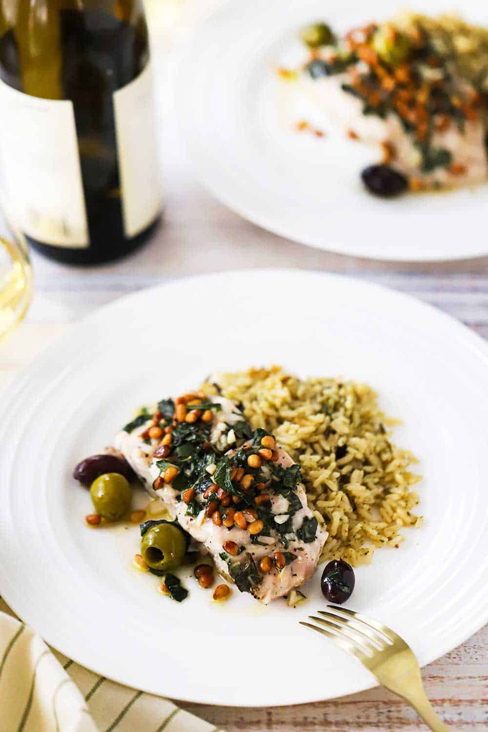 Two white dinner plates filled with Mediterranean-style baked red snapper and a mound of cooked wild rice, both sitting next to a bottle of wine.