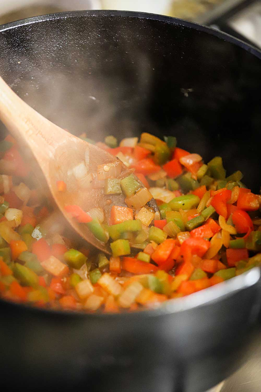 A large black cast-iron pot filled with chopped green and red peppers simmering with a large wooden spoon stirring it all.