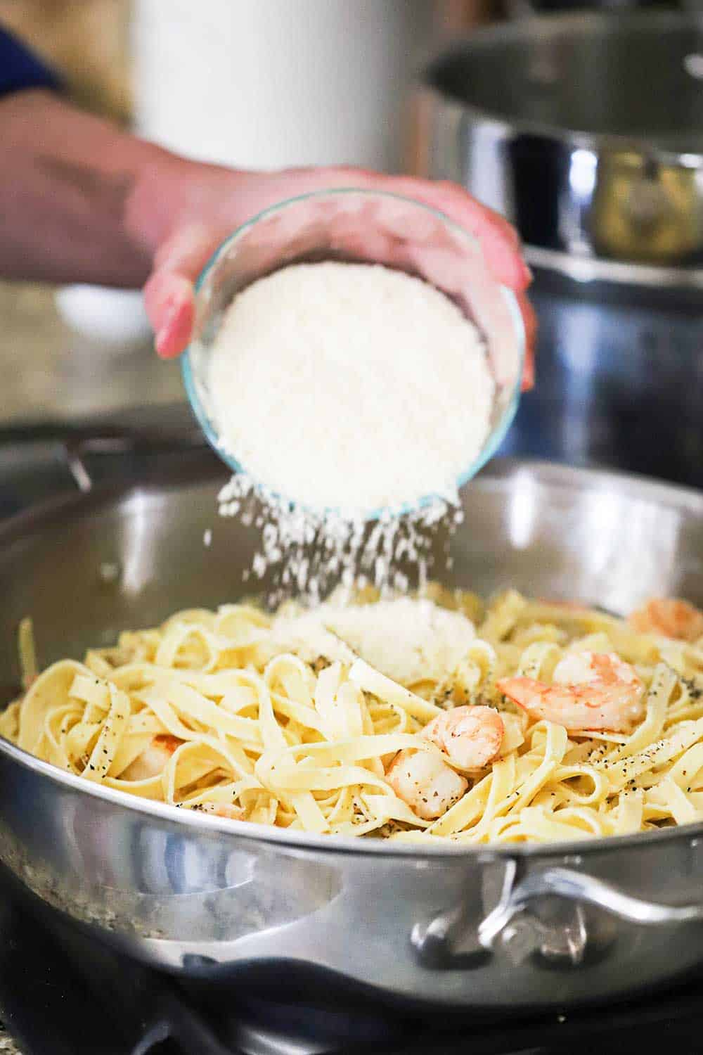 A person transferring a cup of grated Parmigiano-Regianno cheese into a skillet of cooked shrimp and fettuccine in a light cream sauce.