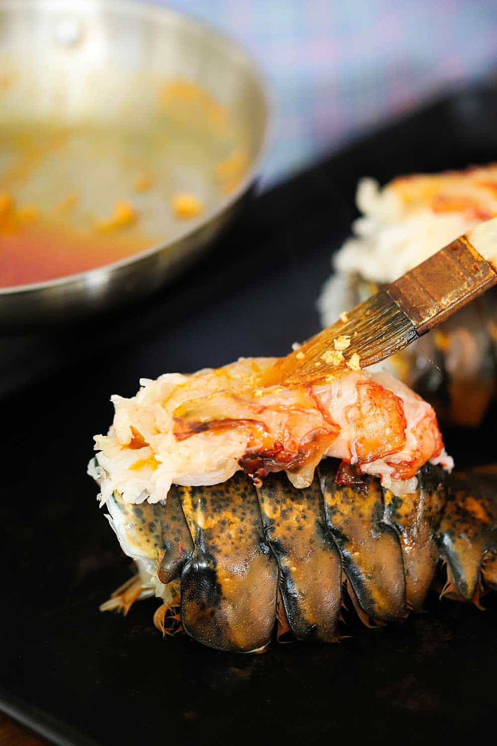 A person brushing melted butter with paprika onto the exposed flesh of a lobster sitting on top of the tail.