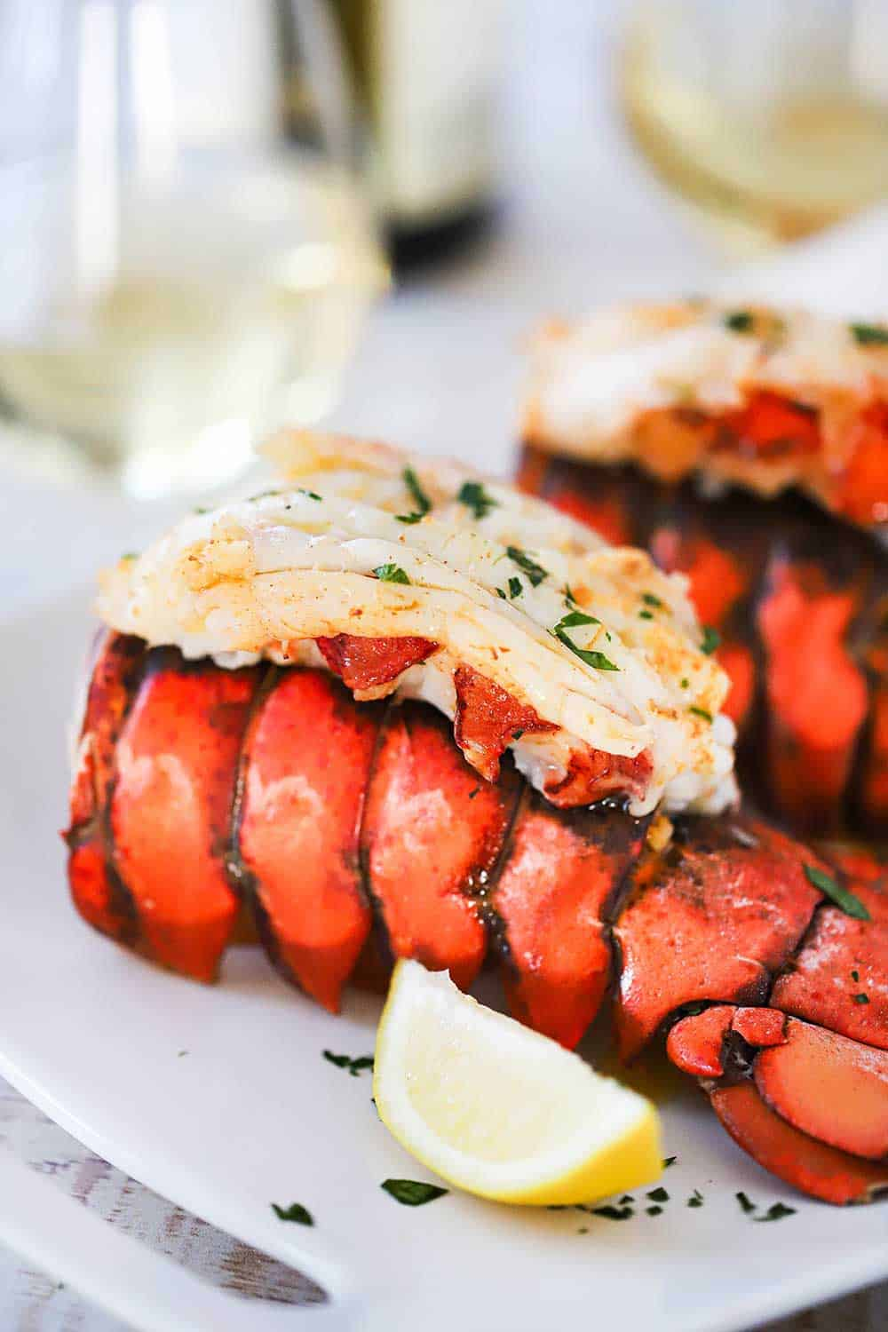 An 8 oz. fully cooked lobster tail with the meat sitting on top of the tail all on a white dinner plate with a lemon wedge.