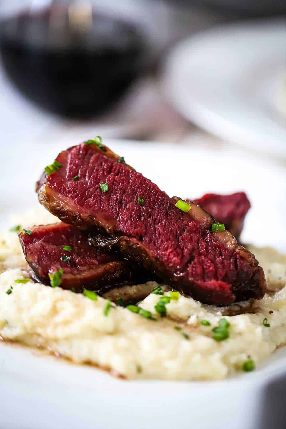 Two slices of Wagyu chuck short ribs that are stacked on top of mashed cauliflower all on a white dinner plate.