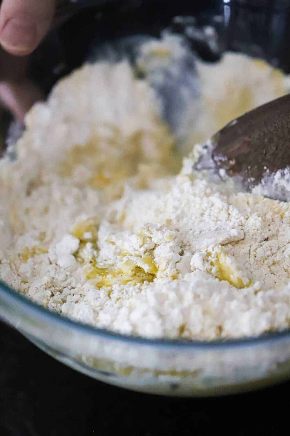 A glass bowl filled with flour, water, yeast, and cornmeal all being mixed together by a wooden spoon.
