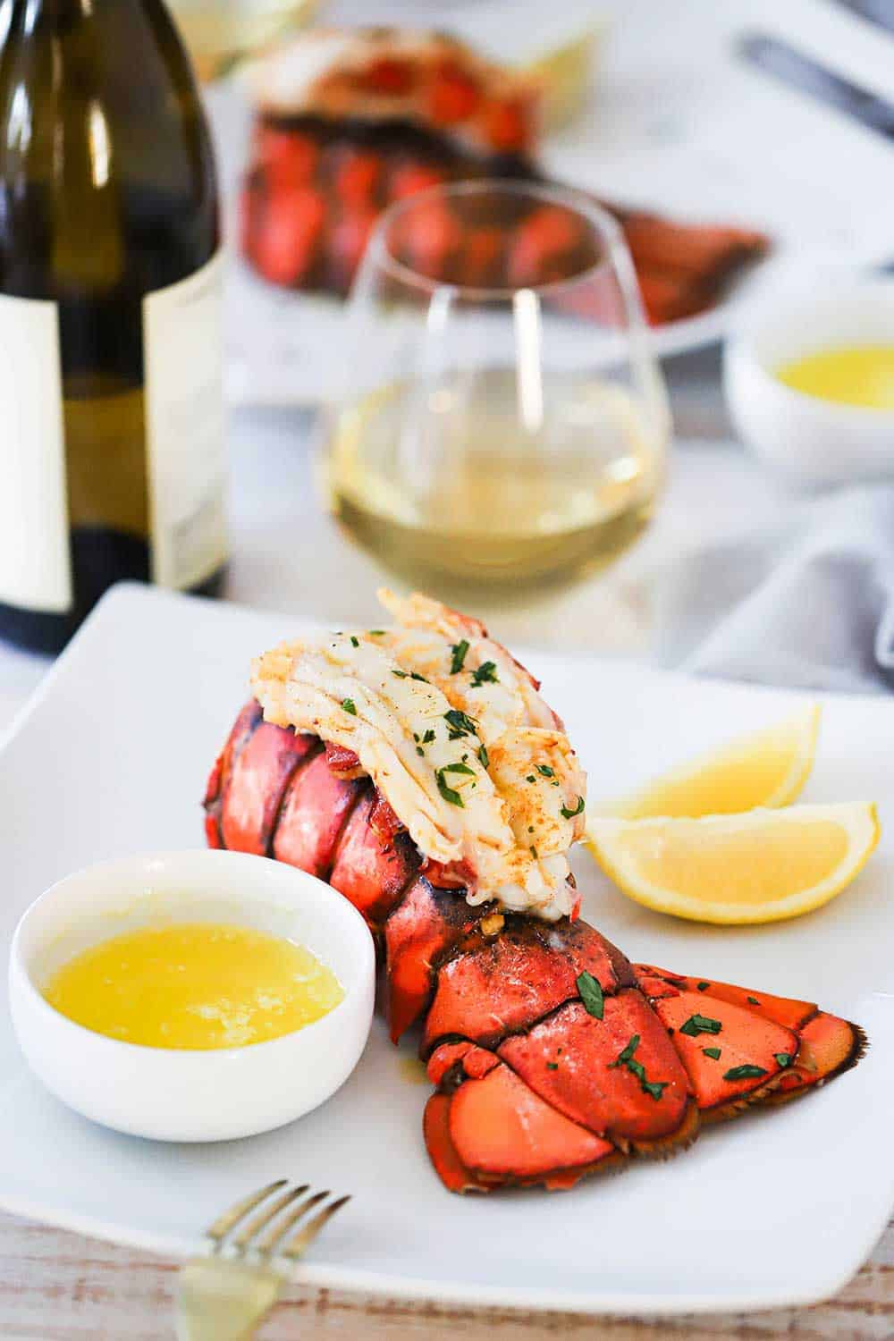 A square white dinner plate filled with a fully cooked lobster tail with a small bowl of drawn butter and lemon wedges next to it, all next to a glass of white wine.