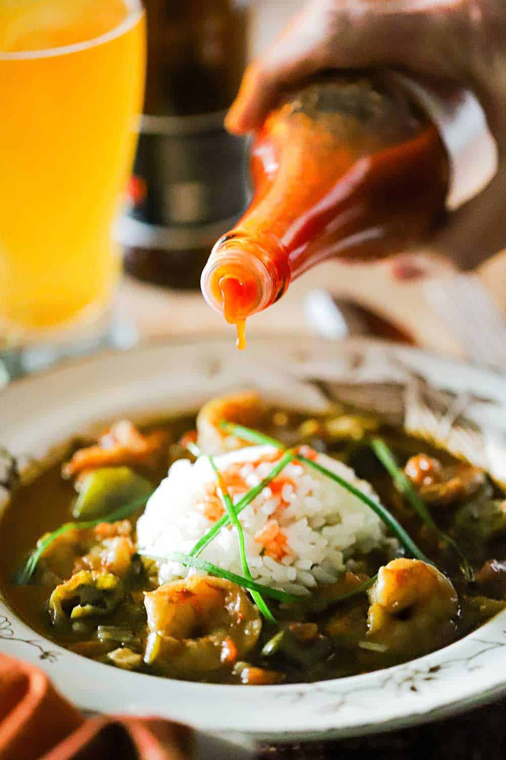 A bottle of Crystals hot sauce is being poured onto a bowl filled with shrimp gumbo with a mound of white rice in the middle.