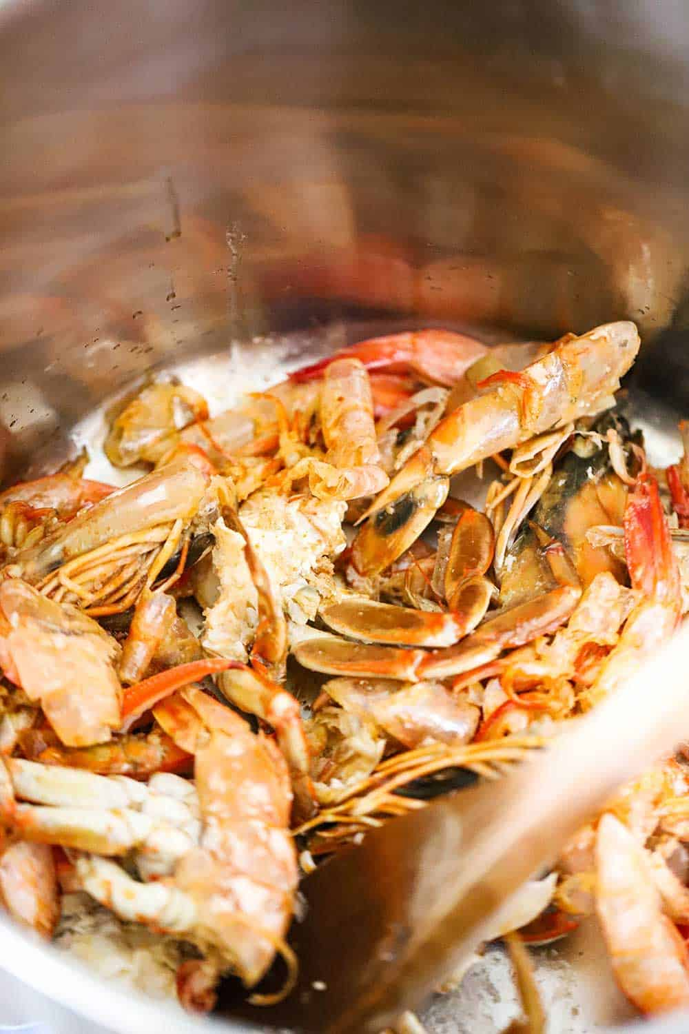 Shellfish shells being sautéed in a large stock pan with a wooden spoon in it.