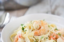 A white individual pasta bowl filled with shrimp fettuccine alfredo next to a large silver skillet filled with the same.