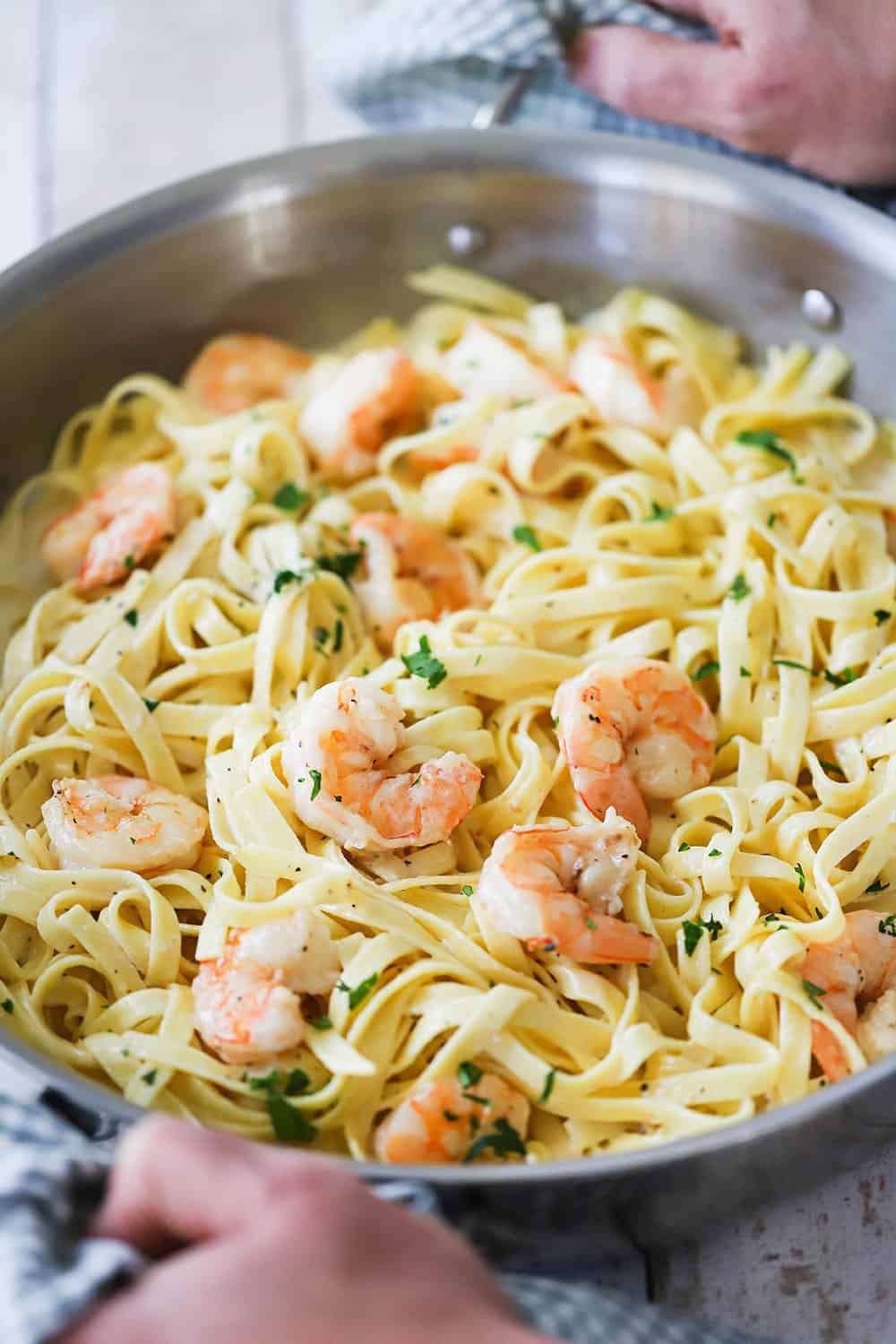 Two hands holding a large stainless steel skillet filled with shrimp fettuccine alfredo.