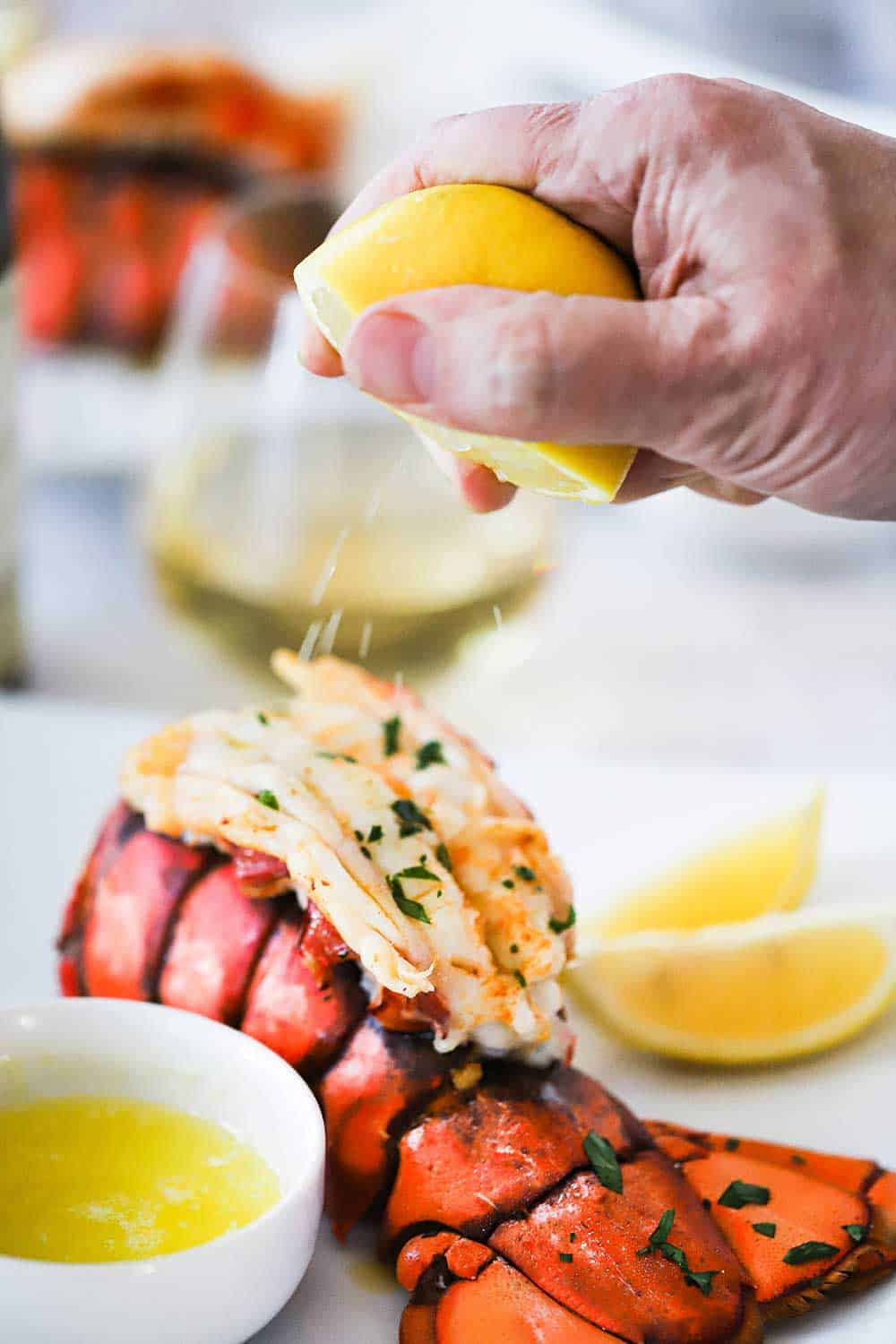 A person squeezing a half of a fresh lemon over a cooked lobster tail sitting next to a small bowl of drawn butter.