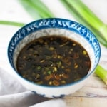 A small colorful Asian bowl filled with hot and sweet dipping sauce next to several scallions.
