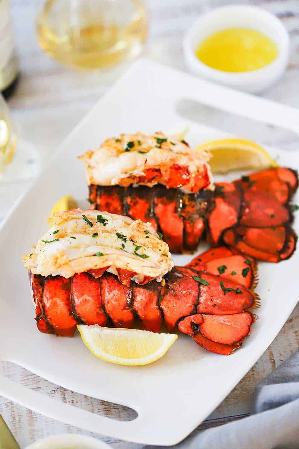 Two fully cooked lobster tails with meat on top of the lobster tail, all sitting on a platter next to lemon wedges and melted butter.