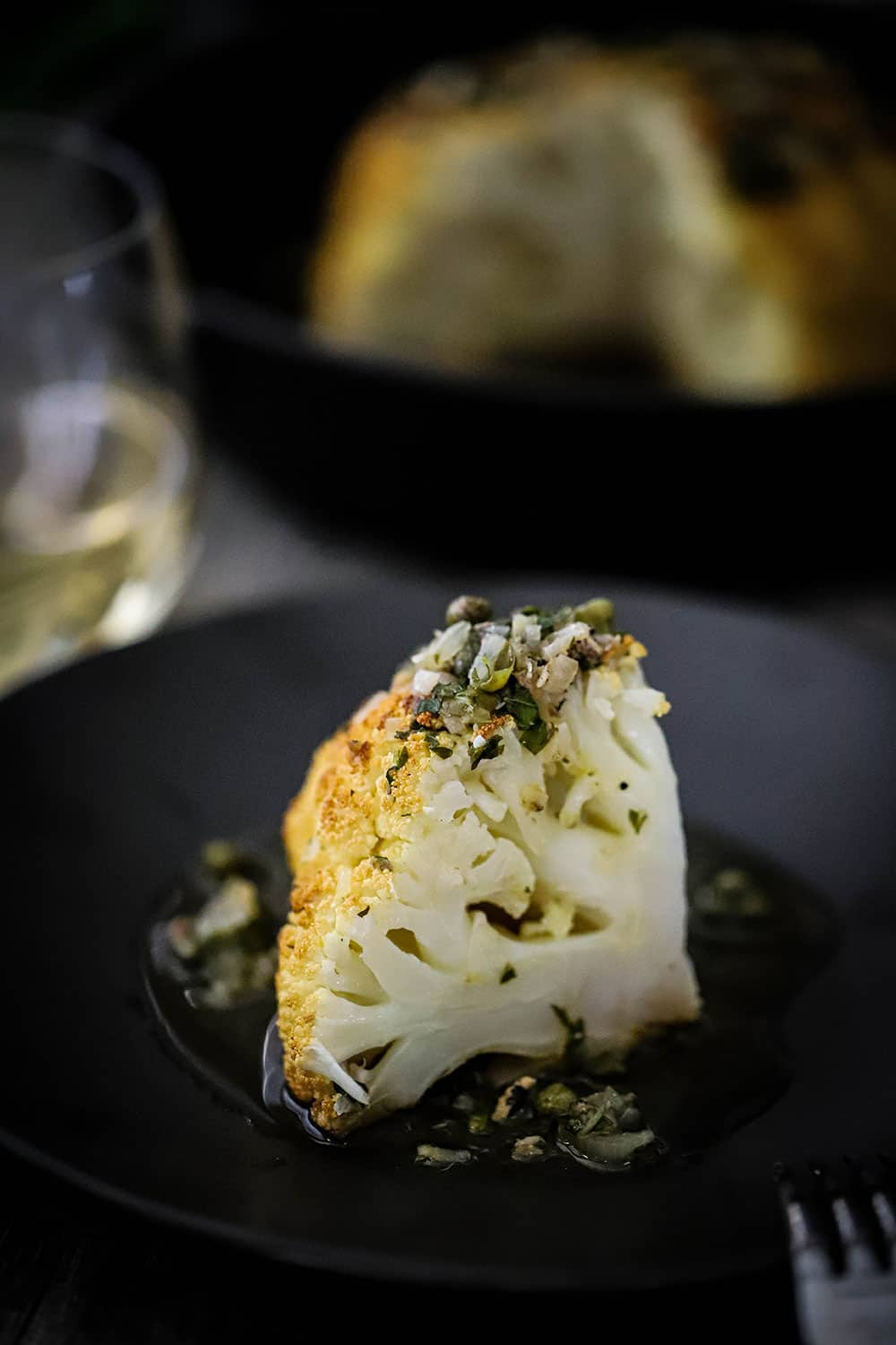 A slice of roasted whole cauliflower sitting on a black plate and topped with a wine butter herb sauce.