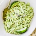 An oval white serving bowl filled with avocado-lime slaw with a gold spoon inserted on the side and a lime wedge on the other side.