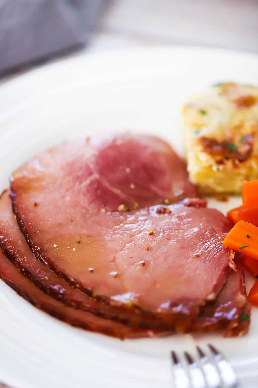 A white dinner plate filled with several slices of baked ham next to au gratin potatoes and braised carrots.