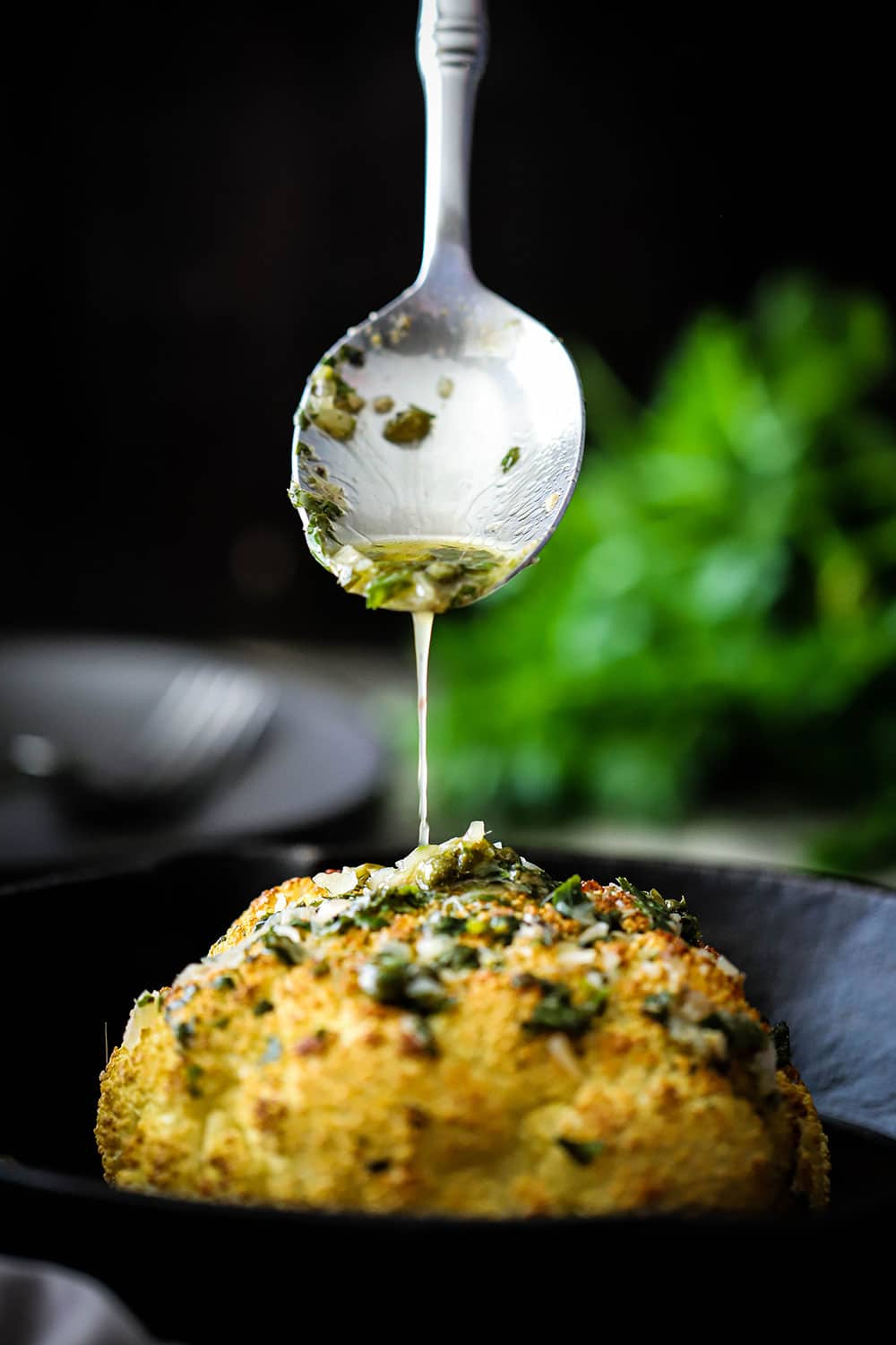 A silver serving spoon pouring a white wine butter and herb sauce over a roasted whole head of cauliflower.