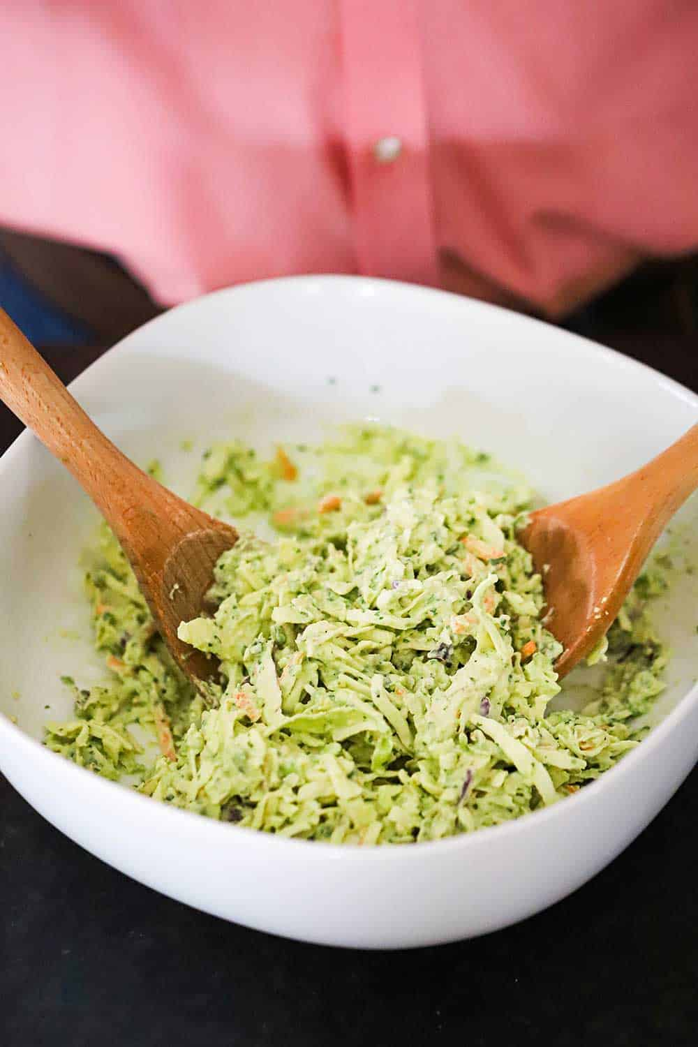 A person in a pink shirt standing behind a white serving bowl filled with avocado-lime slaw with two wooden spoons inserted in it.