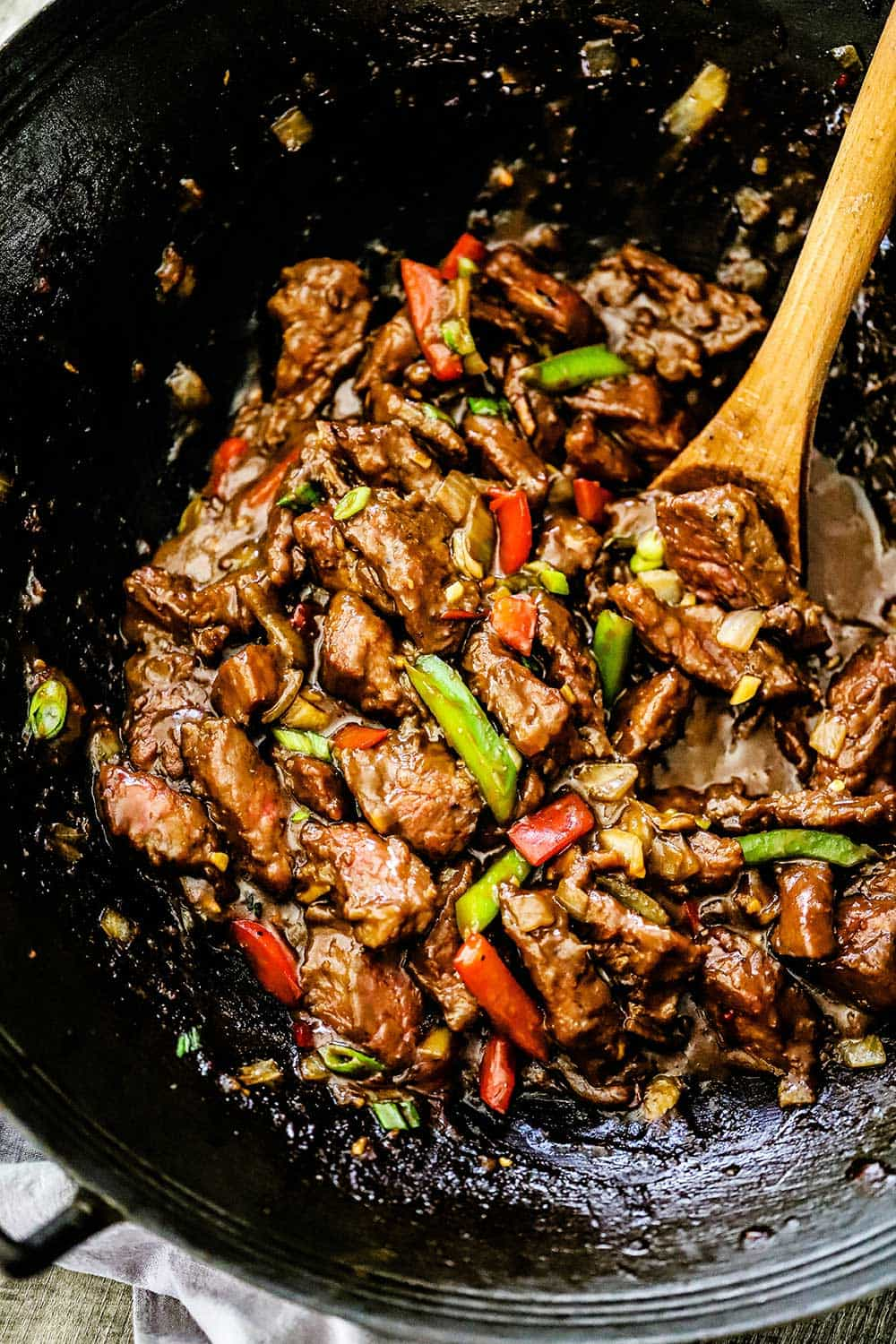 A wok filled with fully cooked mongolian beef with a wooden spoon inserted into the mixture.