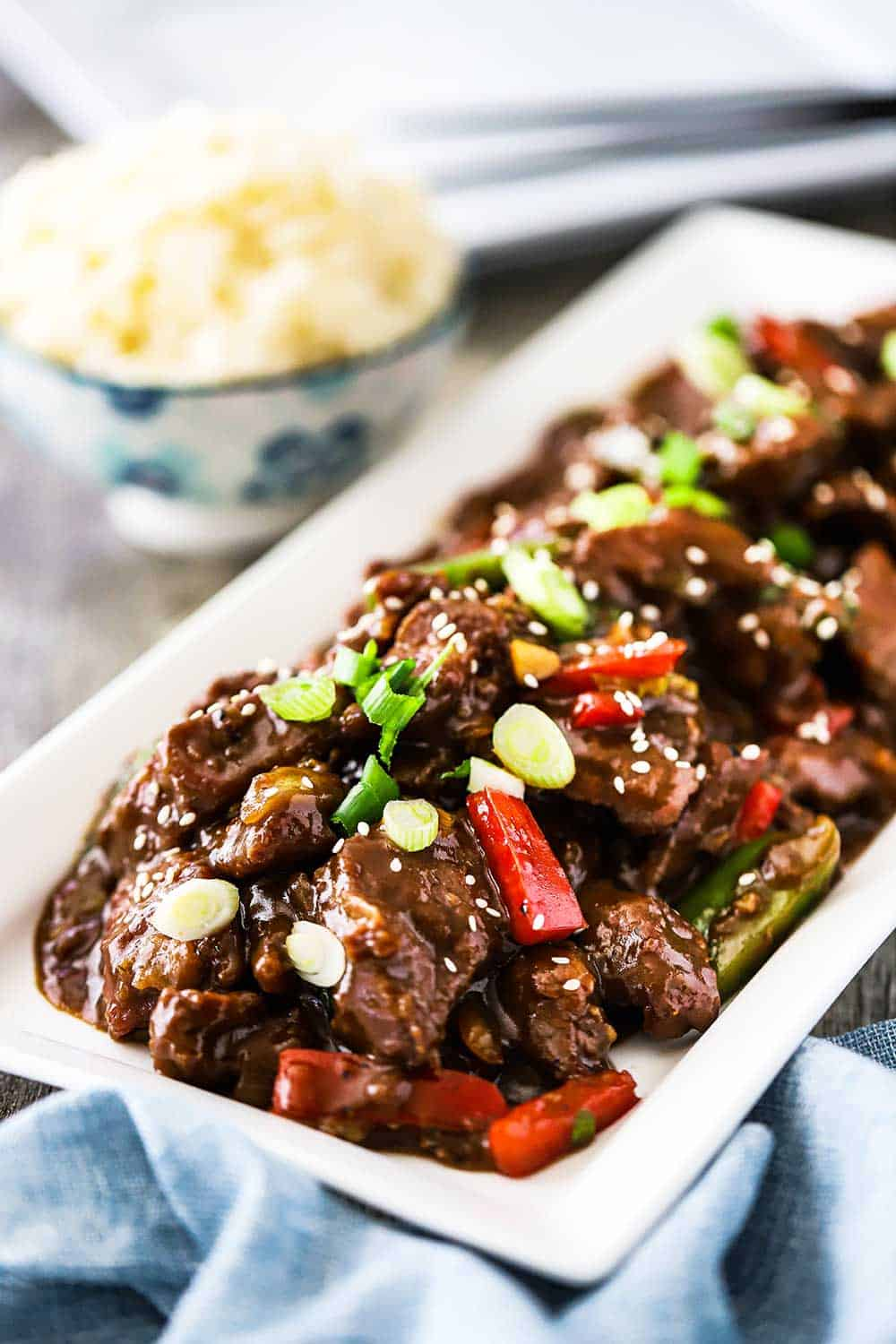 A white rectangular platter filled with prepared Mongolian beef and garnished with snipped chives and white sesame seeds.