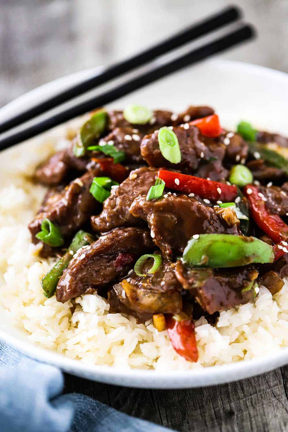 A white circular bowl filled with white rice topped with Mongolian Beef next to a pair of chop sticks.