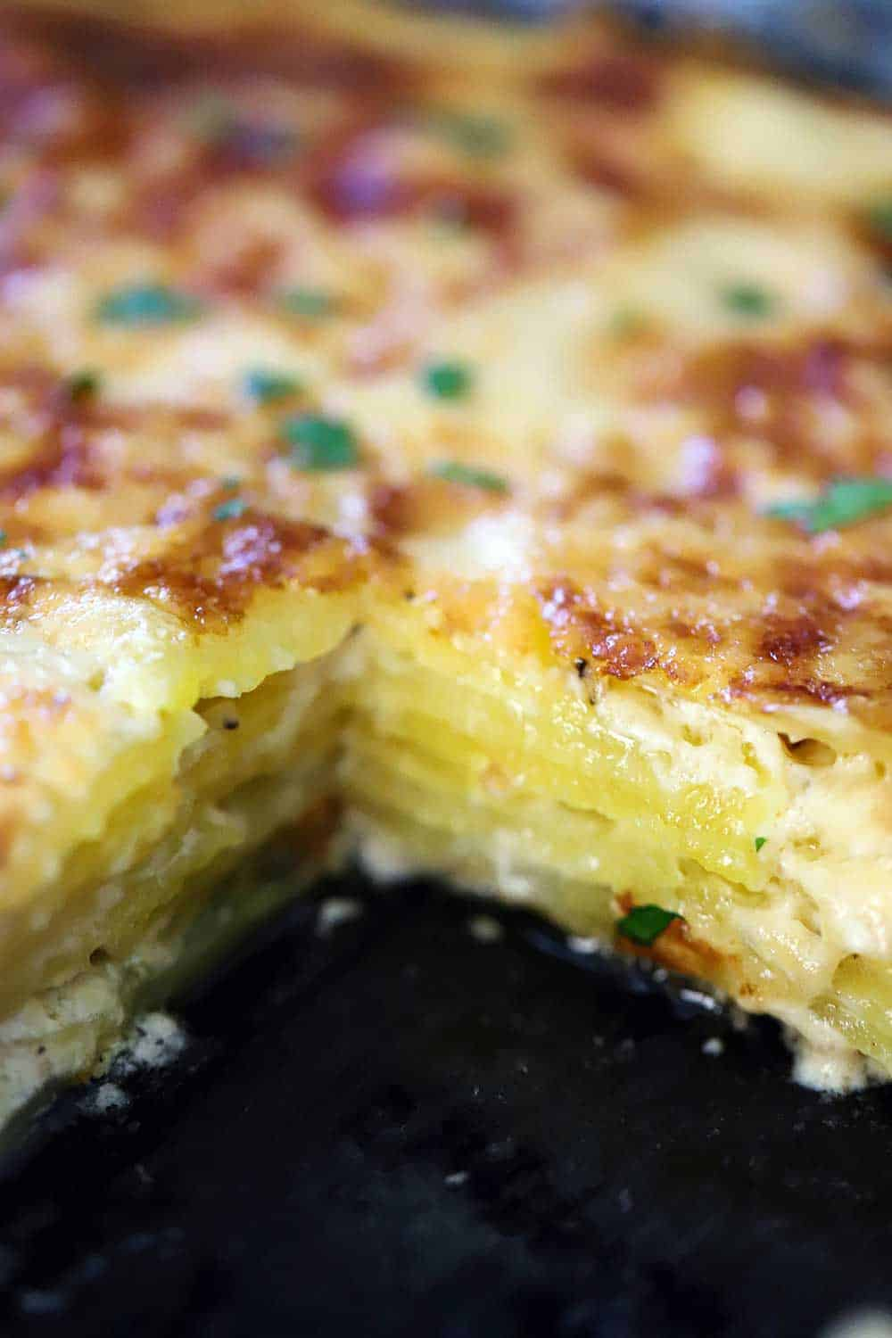 A dark baking dish filled with layers of potatoes dauphinoise with a square piece missing.