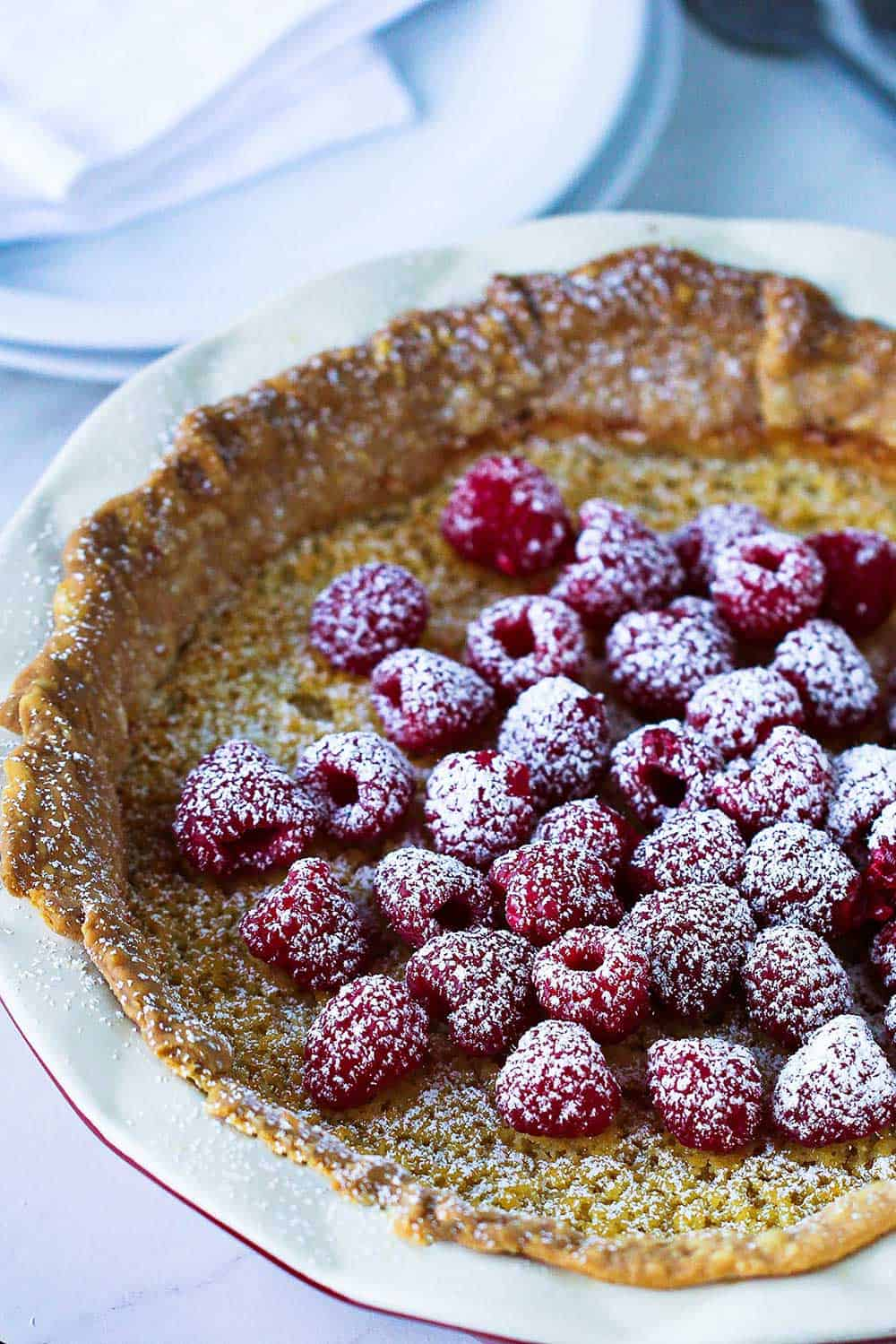 A whole chess pie topped with fresh raspberries and sprinkled with powdered sugar.