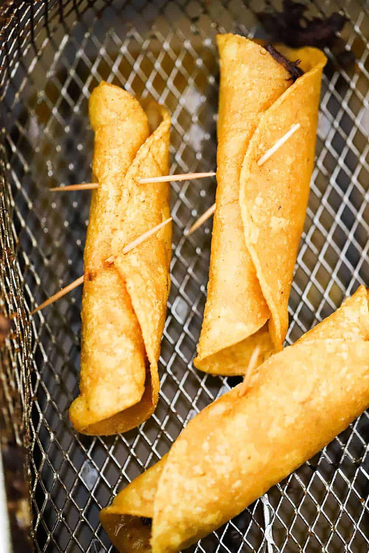 Three rolled fried flautas in a deep fryer basket.