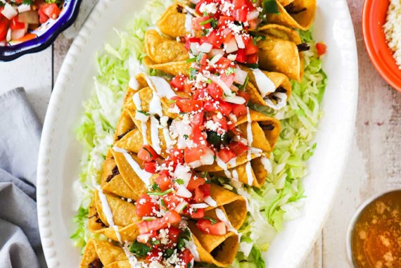 An oval white platter with a layer of shredded lettuce on the bottom topped with a row of chicken flautas surrounded by bowls of salsa, guacamole, and pico de gallo.