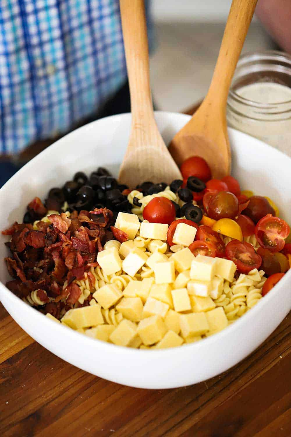 A large white serving bowl filled with pasta topped with cubed cheese, crumbled cooked bacon, sliced black olives, and halved cherry tomatoes.