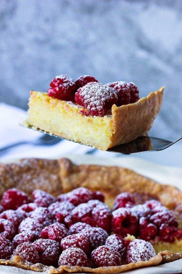 As slice of Chess Pie topped with raspberries and a sprinkling of powdered sugar being raised from the pie on a metal spatula.