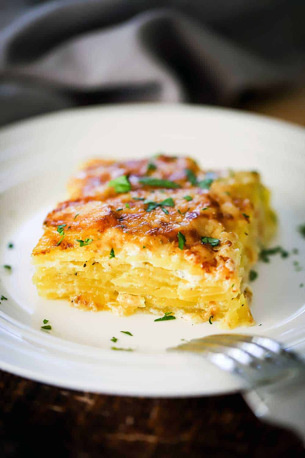 A square serving of potatoes dauphinoise on a white plate garnished with chopped parsley.