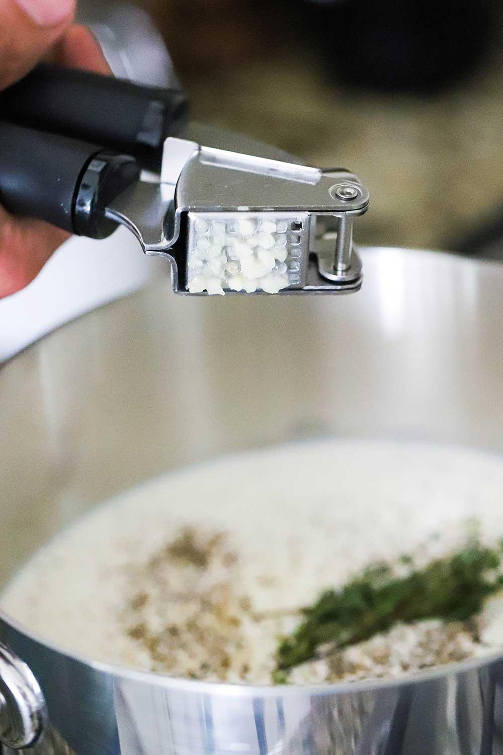 A person squeezing garlic out of a garlic press into a pan filled with cream and herbs.