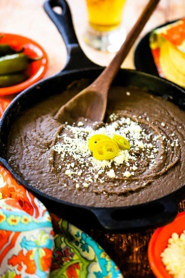 A cast-iron skillet filled with refried beans and topped with crumbled Cojita cheese and several jalapeno slices.