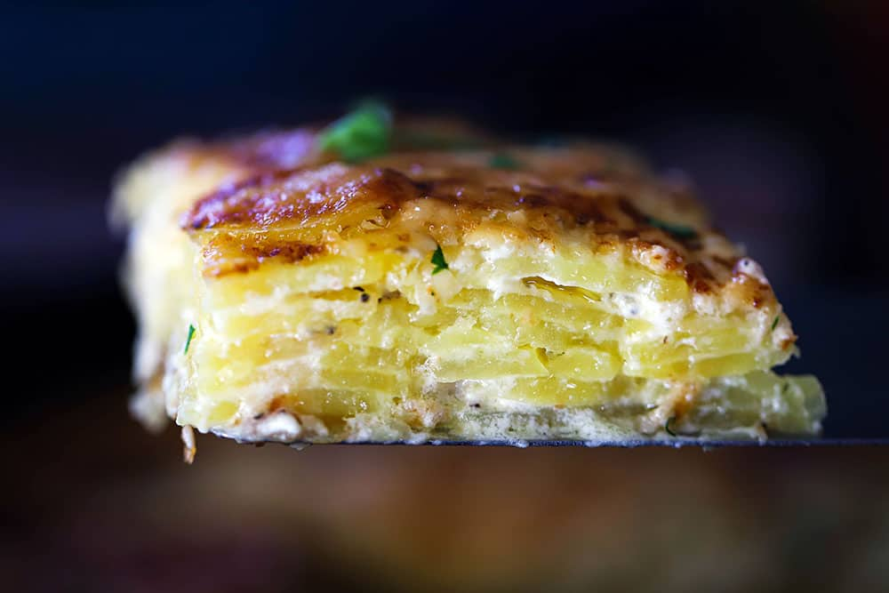A slice of potatoes dauphinoise being raised up on a spatula.