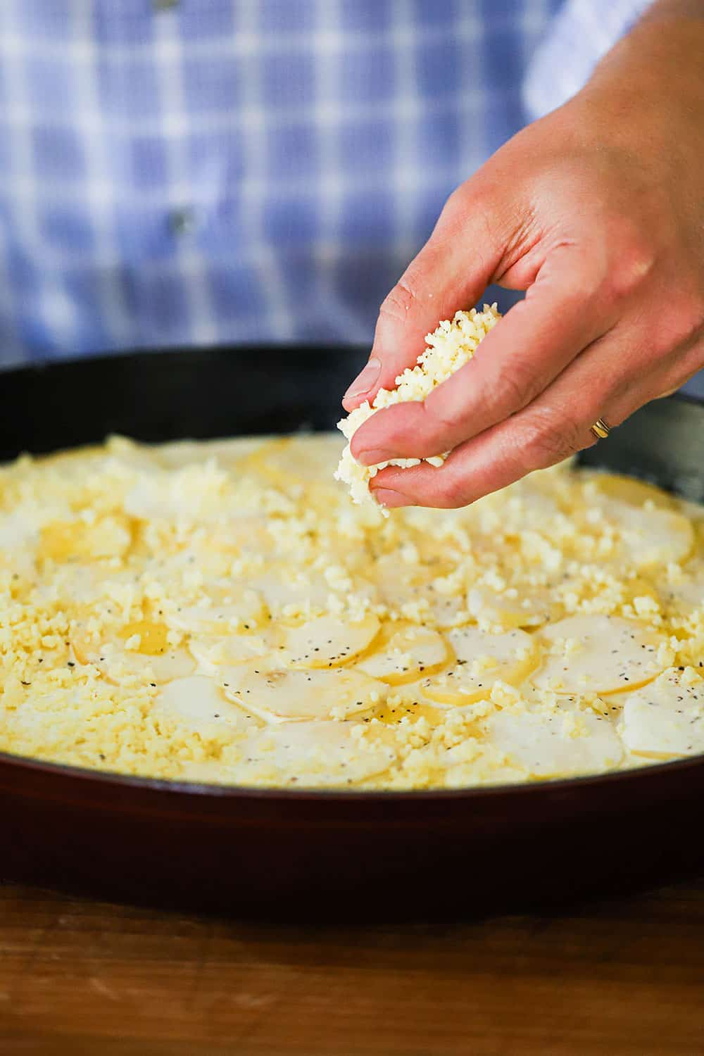 A person sprinkling shredded Gruyere cheese over layers of potatoes in cream all in a oval baking dish.