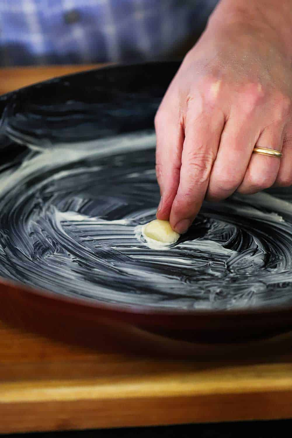 A hand pressing a halved clove of garlic in the bottom of a buttered oval baking dish.