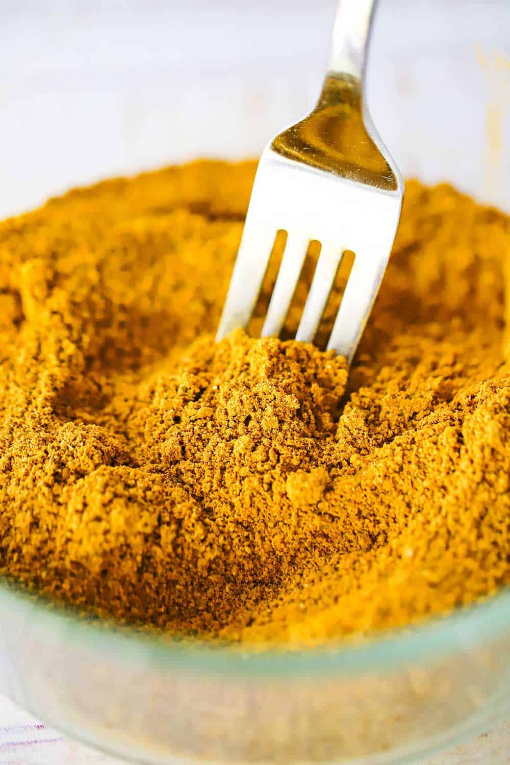 A glass bowl filled with Jamaican curry powder with a fork inserted into the middle of it.
