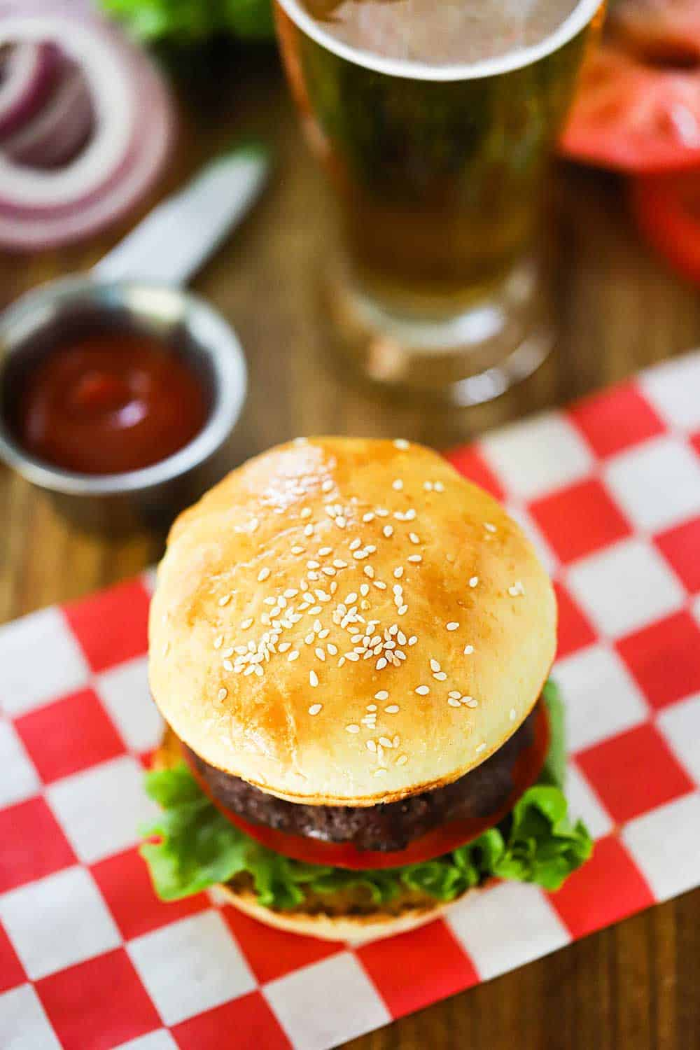 A hamburger sitting on top of a red checkered napkin and next to a small bowl of ketchup.